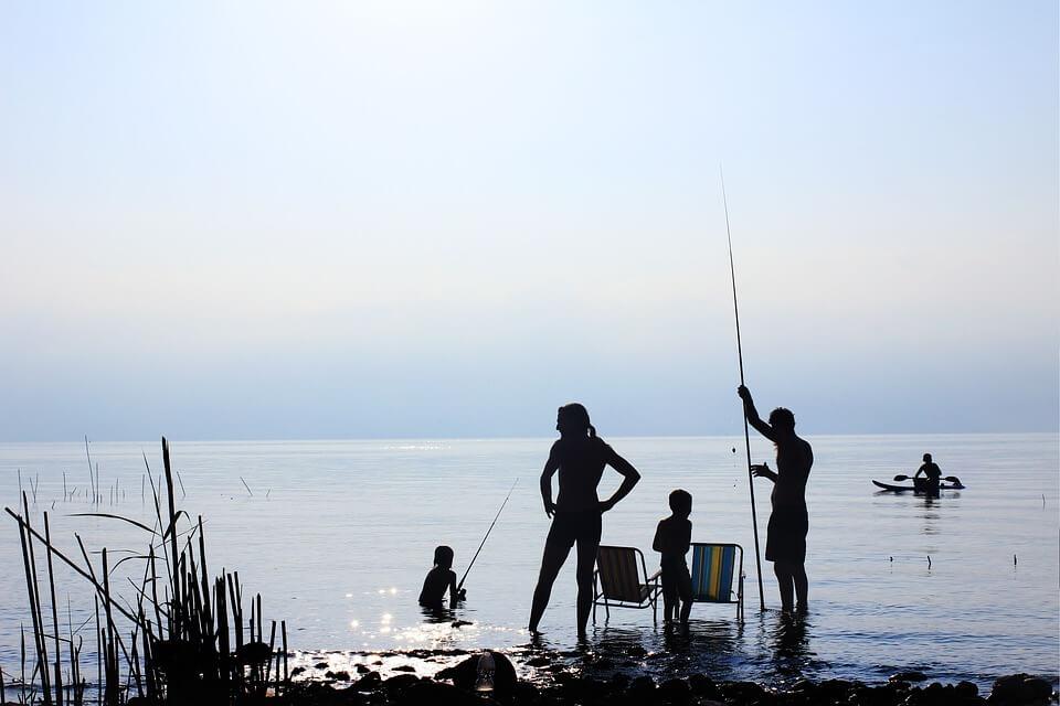 זוג הורים עם שני ילדים דגים בים