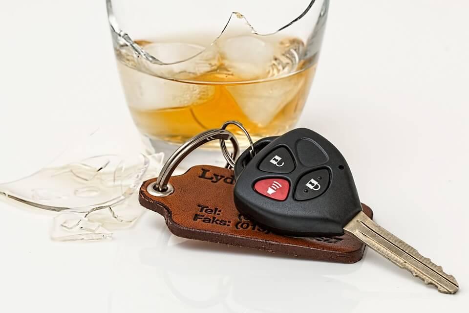 כוס וויסקי עם קרח ולידה מפתח של רכב